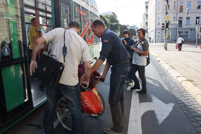 Christian Hausmann (ganz links) und Burkhard Lischka (3.v.l.) helfen Andreas Poppe beim Einsteigen in die Straßenbahn Linie 6 in Richtung Diesdorf.